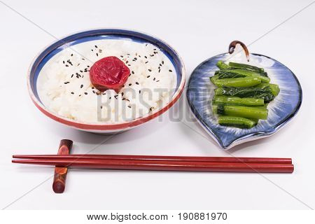 Japanese cuisine Japanese white rice and Traditional Japanese Umeboshi (plum pickle) and Pickle of traditional vegetables Chopsticks or equipment for eating is placed with white background.