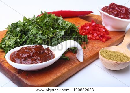 Fresh green cilantro, coriander leaves, tomato paste, chili pepper and spices on a wooden board. Ingredients for meat sauce