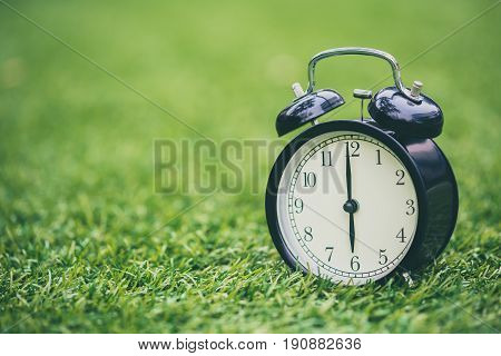 Retro Clock On Green Grass Time At 6 O'clock.