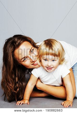 young pretty stylish mother with little cute blond daughter hugging, happy smiling real family, lifestyle people concept close up