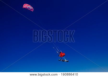 Snowboarder with a kite on fresh snow in the winter in the tundra of Russia against a clear blue sky. Teriberka Kola Peninsula Russia. Concept of winter sports snowkite.