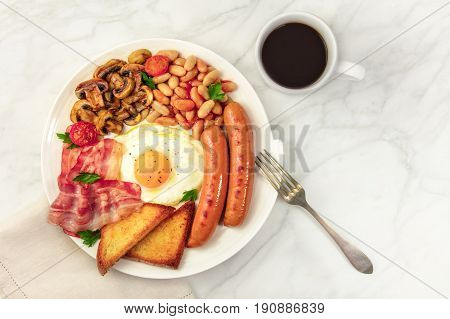 An overhead photo of a plate of English breakfast on a white marble texture, with a sunny side up egg, sausages, bacon, toasts, grilled mushrooms and tomatoes, a fork, a cup of coffee, and copy space