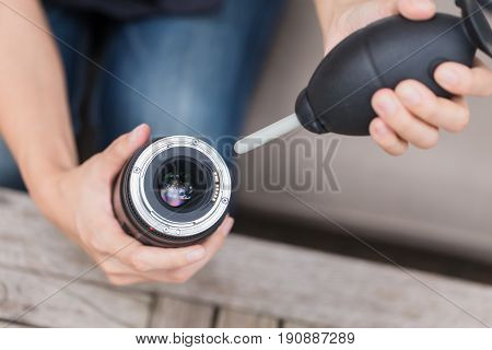 photographer cleaning camera lens with air blower.