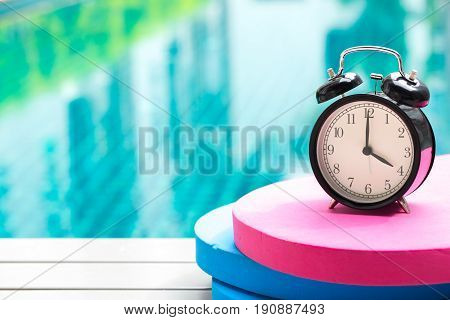 Swimming Times, Retro Black Bell Clock Time At 4 O'clock At Swimming Pool Blur Background.