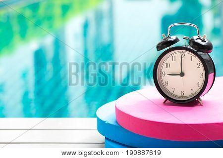Swimming Times, Retro Black Bell Clock Time At 9 O'clock At Swimming Pool Blur Background.