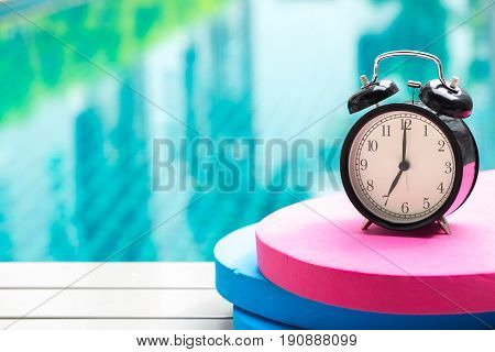 Swimming Times, Retro Black Bell Clock Time At 7 O'clock At Swimming Pool Blur Background.