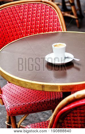 Parisian cafe terrace with red wicker chairs and an espresso on the table