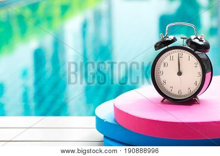 Swimming Times, Retro Black Bell Clock Time At 12 O'clock At Swimming Pool Blur Background.