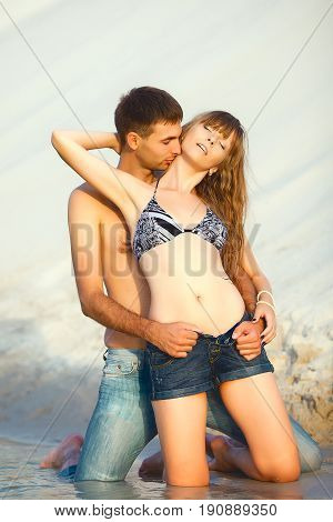 romantic lovers on travel honeymoon vacation summer holidays romance. Young happy girl and man kissing and embracing on water