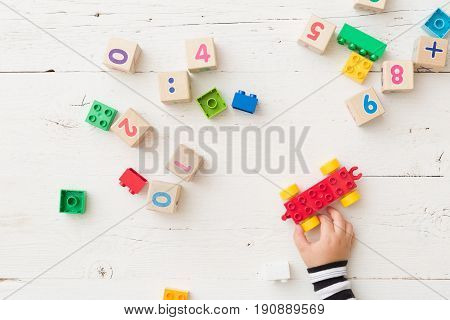 Top view on child's hand playing with wooden cubes with numbers and colorful toy bricks on white wooden background. Baby with toys
