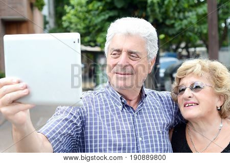 Portrait of an old couple taking selfie with digital tablet. Outdoors.