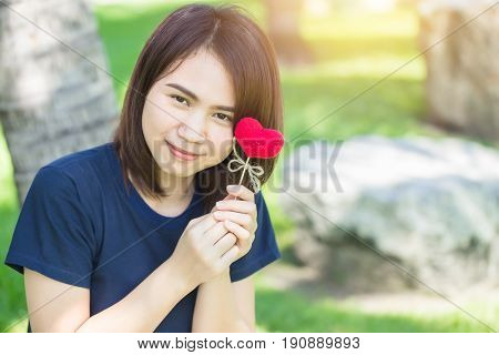 new friend love meeting and date cute smile Asian Thai teen hand hold red heart sweet loving symbol of take care or charity help to you.