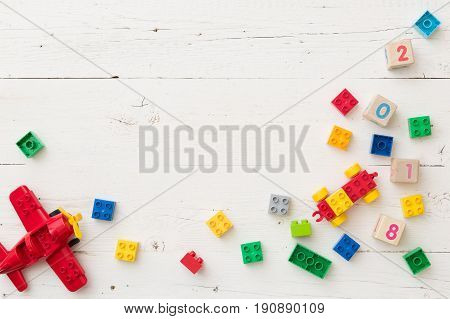 Top view on wooden cubes with numbers and colorful toy bricks and plane on white wooden background. Toys in the table
