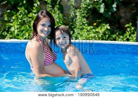 Cute Child And His Pregnant Mom, Swim In Swimming Pool