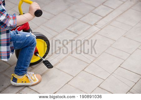 Small toddler boy riding his toy bicycle on street concrete. Child learning to ride a bike.