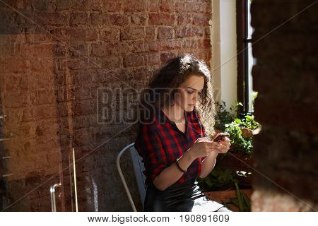 Portrait of curly young female student in plaid shirt chatting with friends using wireless connection to 4G internet sitting in cafe on brick wall background with copy space for your information