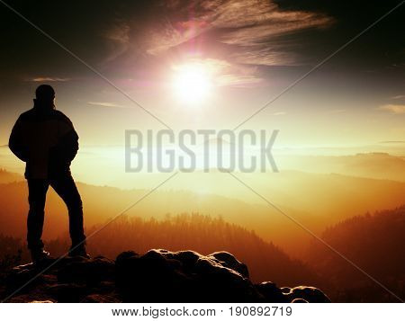 Tall tourist with sporty figure stand on rocky view point. Dark hills in orange misty background. Sunny spring daybreak in rocky mountains.