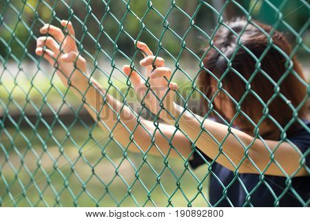 Prison Teen Girl Women In The Cage Hand At Fence Prison In Jail, No Freedom Struggle Concept.