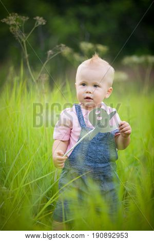 Portrait of cute little blond toddler boy holding paper plane toy on a stick and looking into distance. Adorable child walking in park on sunny day. Summertime Outdoors. Childhood lifestyle concept