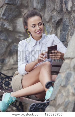 Youth Lifestyle Concepts. Happy Smiling Caucasian Brunette Woman With Headphones Relaxing on Bench and Chatting on Smartphone. Vertical Image Orientation