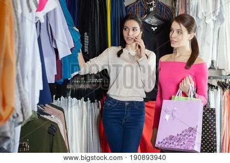 Two Beautiful Walking In The Mall With Bags Of Gifts. Talking On The Cell Phone