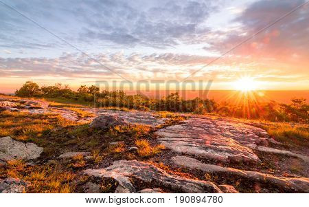 Sun sets over rocky granite outcroppings in early summer at top of New Jersey, High Point State Park