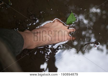 Bare foot in a puddle with reflection of trees and sky.