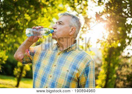 Senior man is drinking water in park.