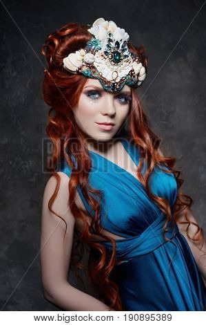 Redhead girl fabulous look blue long dress bright makeup and big eyelashes. Mysterious fairy woman with red hair. Big eyes and colored shadows long lashes. Sexy look Princess on a dark background