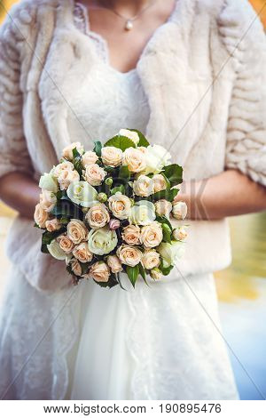 Bridal bouquet. The bride's . Beautiful of white flowers and greenery, decorated with silk ribbon, lies on vintage wooden chair, Festive bouquet of the bride