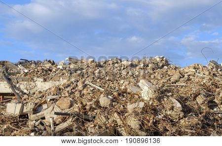 Large mountain demolition of building blocks and curved iron against a blue sky