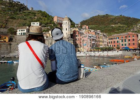 VERNAZZA Italy June 4 2017 : A young couple admires a romantic view of the Cinque Terre National Park on the Italian Riviera. The Cinque Terre area is a very popular tourist destination and a world heritage site.
