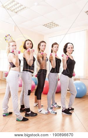 Sport Ideas. Five Female Caucasian Athletes Standing with Barbrells Together in Sport Class. Vertical Image Orientation