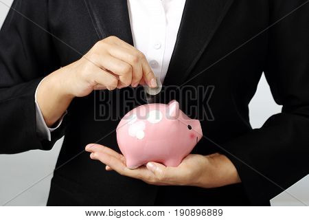 Close up of businesswoman putting a coin into piggy bank on gray background finance theme.
