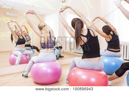 Sport Fitness Wellness and Helathy Lifestyle Concepts. Group of Five Caucasian Female Athletes Having Stretching Exercises with Fitballs Indoors.Horizontal Shot