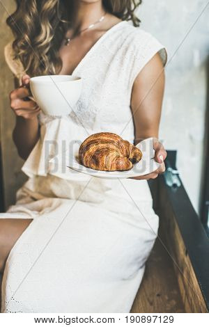 French or Italian breakfast. Young blond woman in white dress holding fresh croissant in plate and cup of cappuccino in cafe