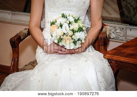Bridal bouquet. The bride's . Beautiful of white flowers and greenery, decorated with silk ribbon, lies on vintage wooden chair, bouquet