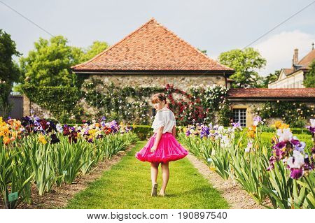 Outdoor portrait of adorable little girl playing in a beautiful flower park on a nice summer day. Fashion kid girl wearing white blouse and bright pink tutu skirt looking back over shoulder