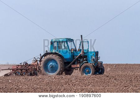 An old tractor in the field plows the land. Spring landscape of a countryside a farm.