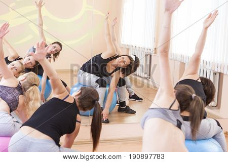 Sport Fitness Helathy Lifestyle Concepts. Group of Five Caucasian Female Athletes Having Stretching Exercises with Fitballs Indoors.Horizontal Shot.