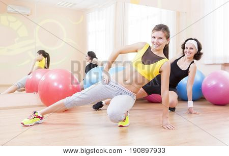 Sport Fitness Healthy Lifestyle Concepts.Two Female Caucasian Athletes in Good Fit Posing With Fitballs in Sport Gym.Horizontal Shot