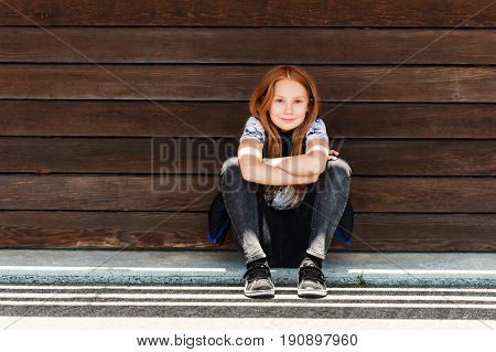 Outdoor fashion portrait of adorable 9 year old red-haired girl
