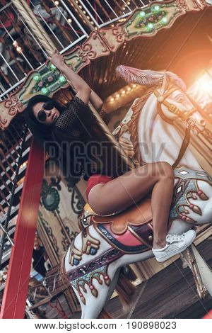 Merry-go-round fun. Attractive young mixed raced woman in red bikini riding merry-go-round