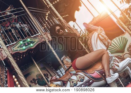 Just for fun. Attractive young mixed raced woman in red bikini riding merry-go-round