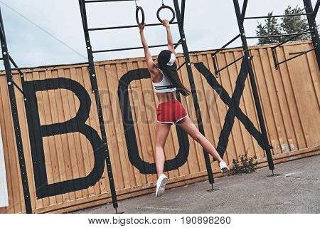 Training body to perfection. Full length rear view of young woman in sports uniform hanging while exercising outdoors