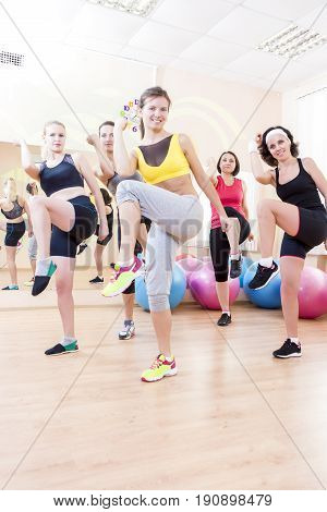 Sport and Fitness Concepts and Ideas. Group of Five Caucasian Female Athletes Having Stretching Exercises in Gym Together.Vertical Image