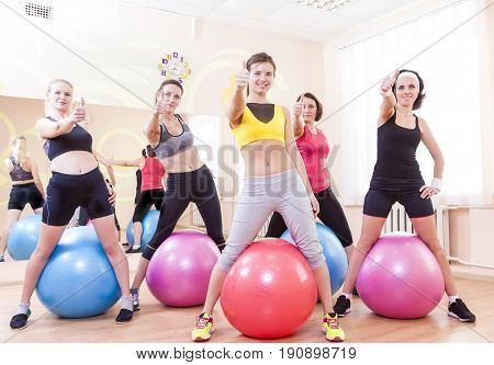 Sport and Fitness Concepts and Ideas. Group of Five Caucasian Female Athletes Having Exercises With Fitballs in Gym and Showing Thumbs Up Sign. Horizontal Image Orientation