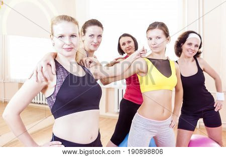 Healthy Lifestyle Concepts. Closeup Portrait of Five Happy Caucasian Female Athletes Posing Together Embraced Against Fitballs in Gym.Horizontal Image Orientation