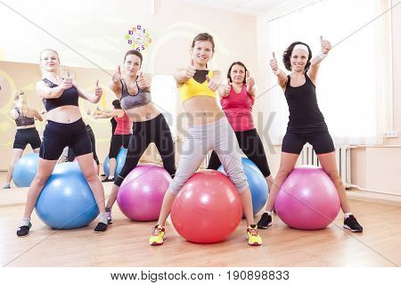 Sport and Fitness Concepts and Ideas. Group of Five Caucasian Female Athletes Having Exercises With Fitballs in Gym and Showing Thumbs Up Sign. Horizontal Shot