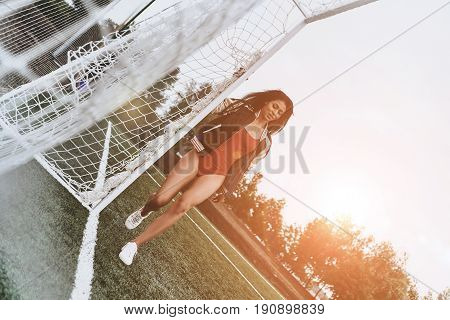 She loves soccer. Full length of attractive young woman in red bikini posing near goal post on the soccer field